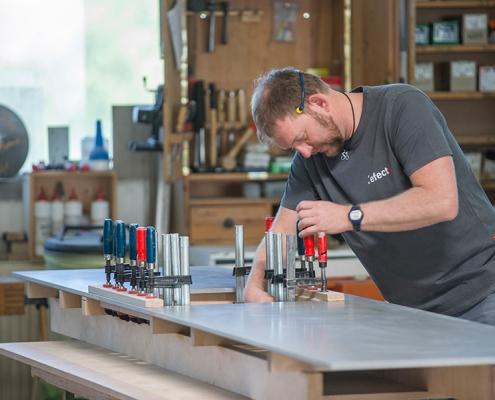 Schreiner bearbeitet Betonplatte